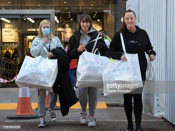 Some of the first shoppers to gain entry to Primark exit the store as thousands of shoppers wait in line on April 30, 2021 in Belfast, Northern...