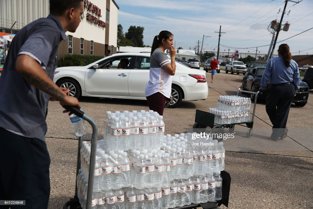 Some of the last bottles of water at the Coastal Industrial and Specialty gas welding supplies store are brought to vehicles as people try to purchase water after the water supply to the city of Beaumont was shut down after Hurricane Harvey passed through on August 31, 2017 in Beaumont, Texas. Harvey, which made landfall north of Corpus Christi August 25, has dumped more than 50 inches of rain in some areas in and around Houston.