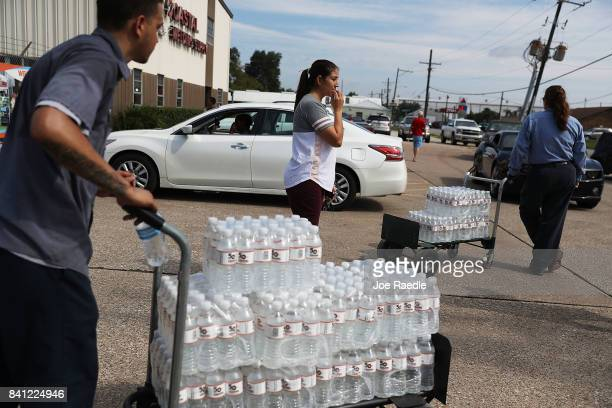 Some of the last bottles of water at the Coastal Industrial and Specialty gas welding supplies store are brought to vehicles as people try to...