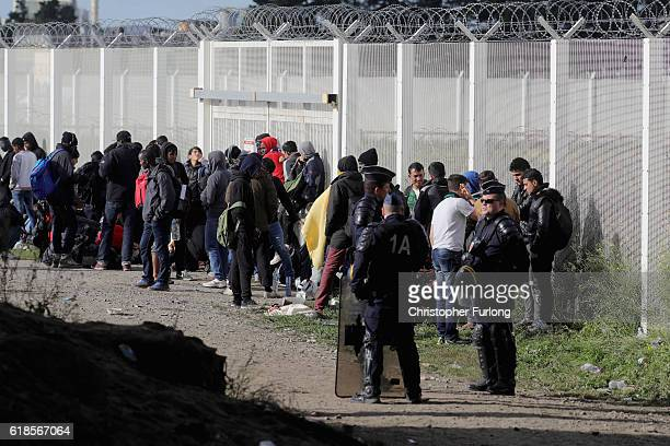 Some of the last remaining migrants of the Calais 'Jungle' wait for transport outside the site on October 27 2016 in Calais France Authorities have...