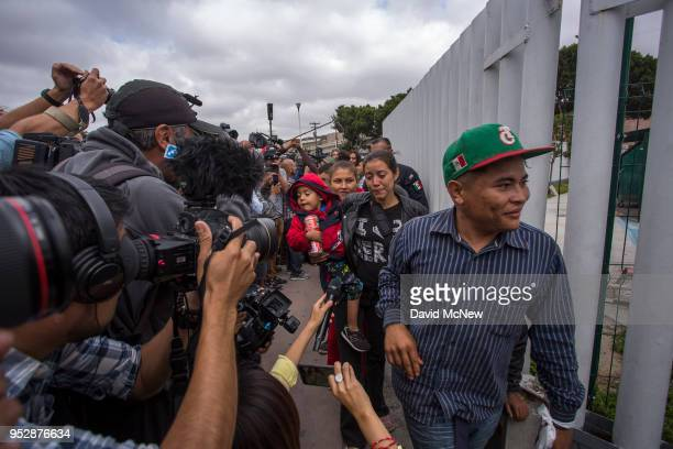 Some of the members of a caravan of Central Americans who spent weeks traveling across Mexico walk past cameras as they walk from Mexico into the US...