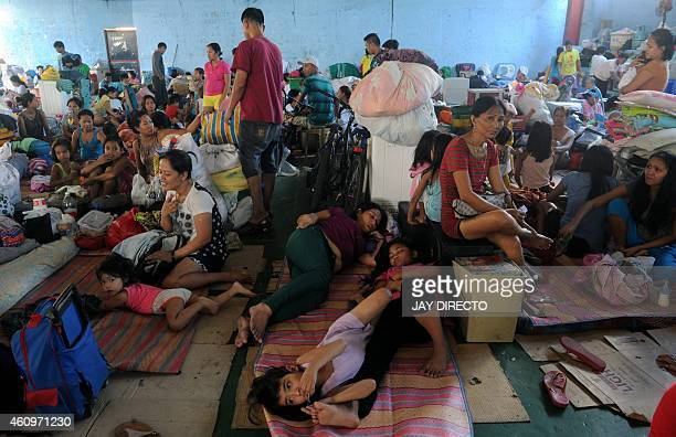 Some of the more than 1500 families made homeless by a fire in a shanty town in Manila seek temporary shelter on a basketball court on January 2 2015...