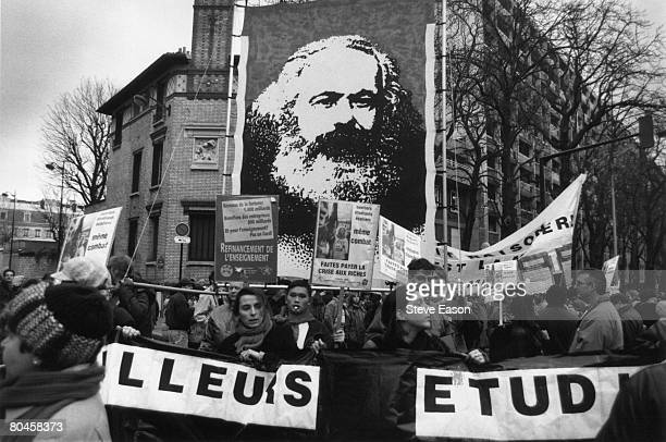 Some of the public sector workers who went on strike against French Prime Minister Alain Juppe's welfare cuts carry a large banner of Karl Marx 16th...