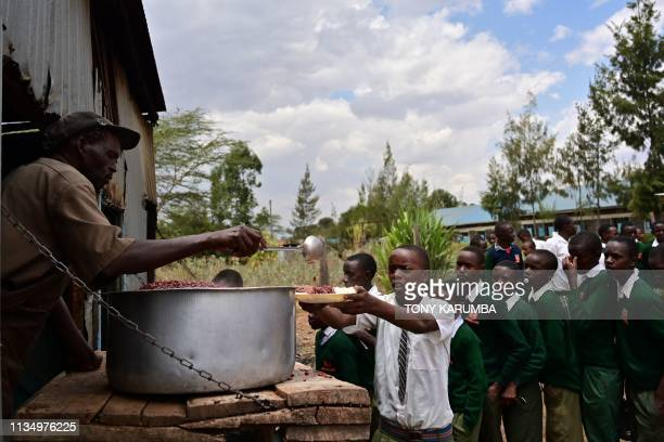 Some of the students of Peter Mokaya Tabichi the Global Teacher Prize Award recipient2019 queue at lunch time with their spoons and plates at Keriko...