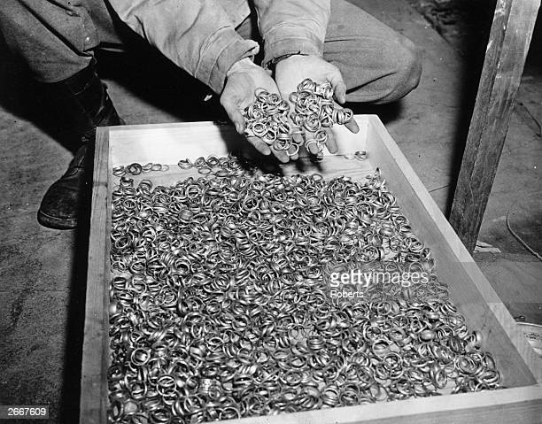 Some of the thousands of wedding rings discovered by troops of the US 1st Army in a cave adjoining Buchenwald Concentration Camp near Weimar The...