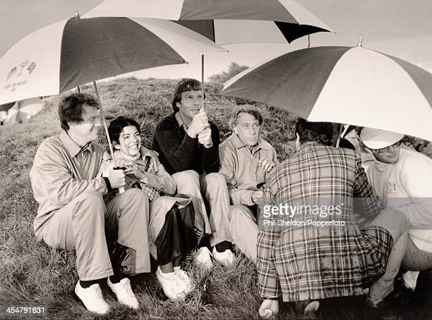 Some of the United States team from left to right Tom Watson with his wife Linda Ben Crenshaw and David Marr sheltering from the rain during the...