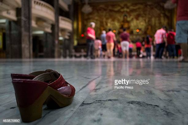 Some of the visitors of the Buddhist temple leave their shoes before going to the altar