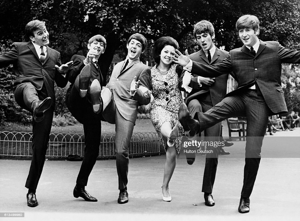 Some of the winners of the 1963 'Melody Maker' poll awards give a high kick for their success. Susan Maugham was voted top female singer, on the far left is Billy J. Kramer (Best Hope for 1964). They are photographed with the Beatles, who were voted top vocal group.