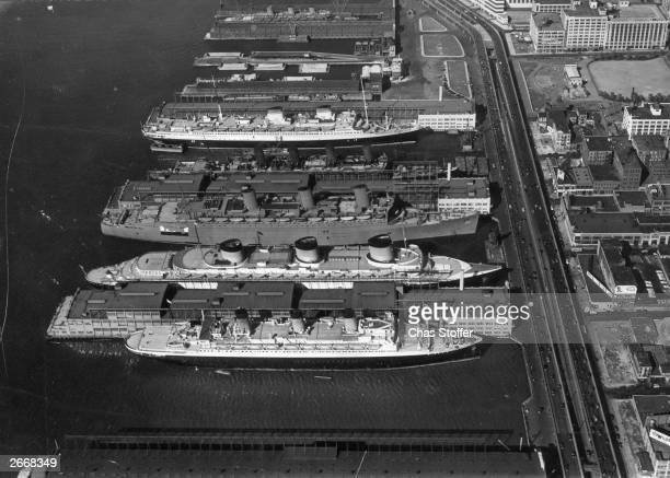 Some of the world's largest ocean liners moored in New York Harbour from front to back the Ile de France the Normandie the Queen Mary the Aquitania...