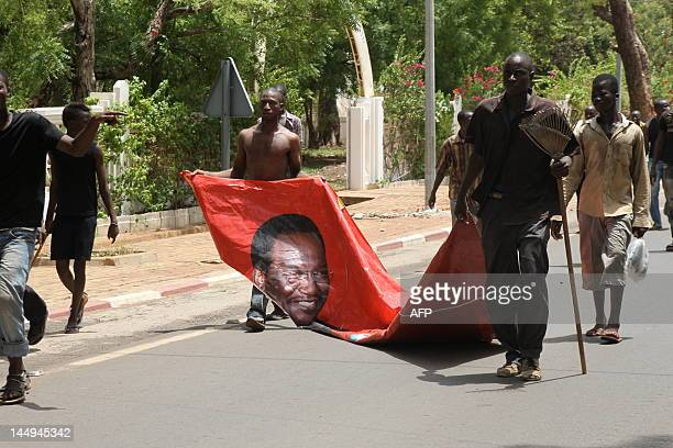 Some of thousands of Malians protest on May 21 2012 in Bamako dragging a portrait of current interim leader Dioncounda Traore against a transition...
