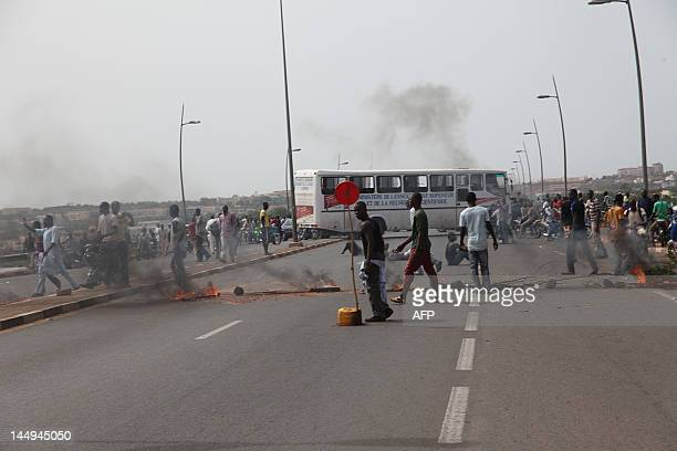 Some of thousands of Malians walk by burning tyres during a protest on May 21 2012 in Bamaka against a transition deal giving coup leader Amadou...