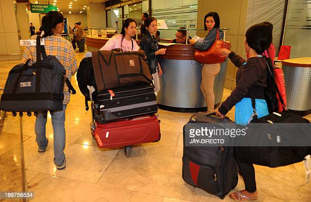 Some on the 30 repatriated Filipino workers arrive at the Manila International Airport on November 4 2013 Thousands of stranded overseas Filipino...