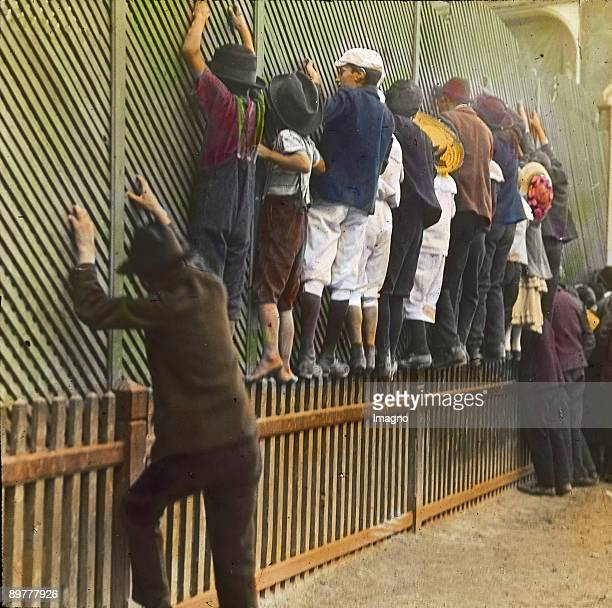 Some onlookers that don't want to pay for on paling fences Viennese Wurstelprater Vienna second district Photograph probably by Emil Mayer...