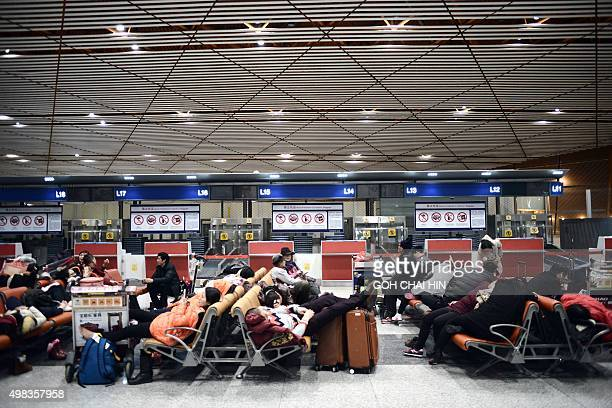 Some passengers sleep as they wait for their flights at the Beijing Capital International airport after heavy snowstorm cancelled and delayed...