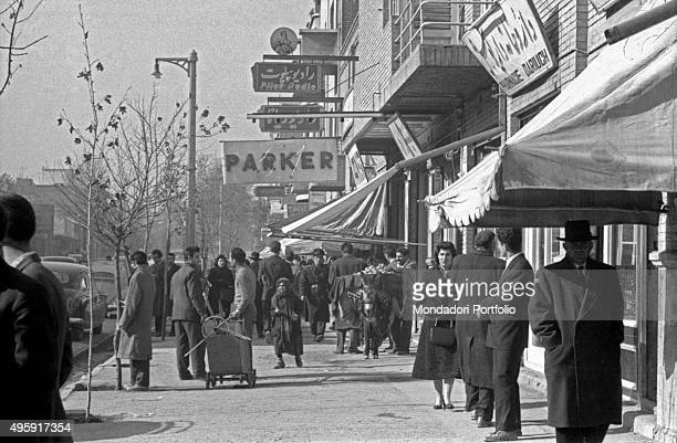 Some passersby walking in a commercial street of the city Tehran 1956