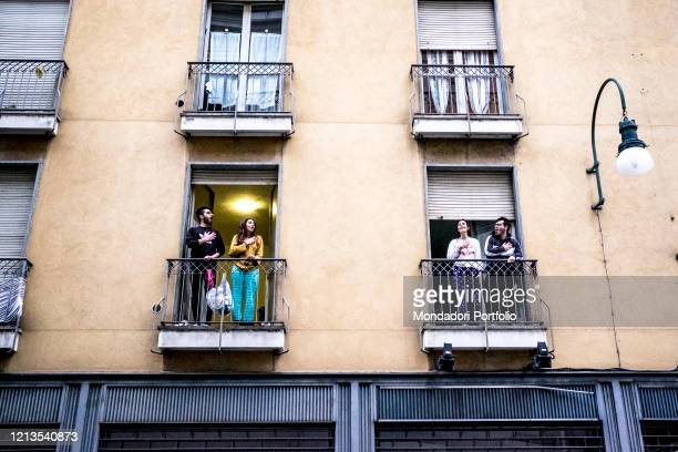Some people appear from the balcony to sing Mameli's anthem during the Coronavirus pandemic . Turin , March 14th, 2020