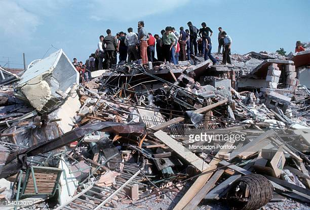 Some people are still above the ruins of a building destroyed by the earthquake FriuliVenezia Giulia May 1976sts Cernobbio April 1965