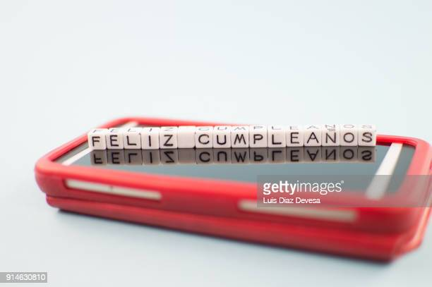 some people are using their mobile phones to congratulate the birthdays in spanish - typographies stock photos and pictures