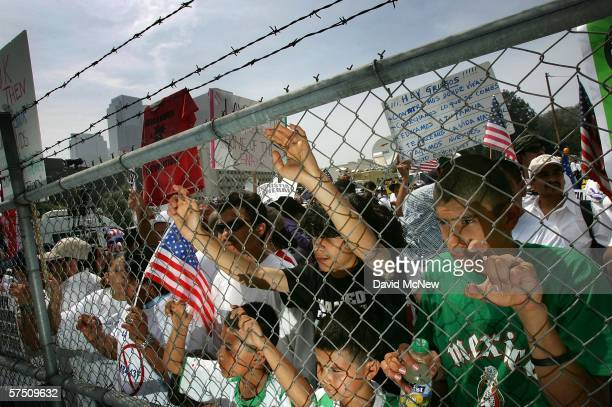 Some people behind a barbedwire and chainlink fence watch the rally on what is dubbed a Day Without Immigrants or the Great American Boycott day on...