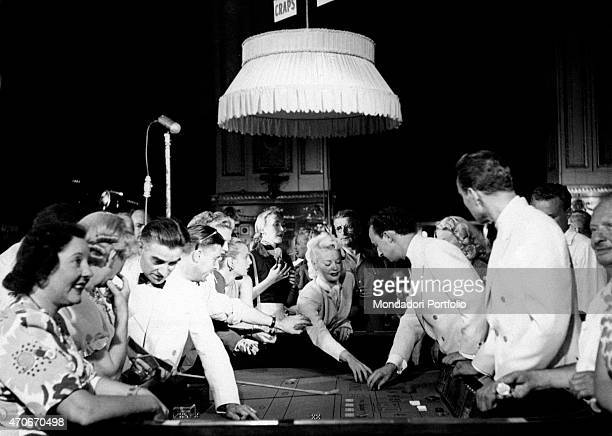 Some people crowd around the game table and make their bets helped by the croupier in the Monte Carlo Casino Principality of Monaco May 1961