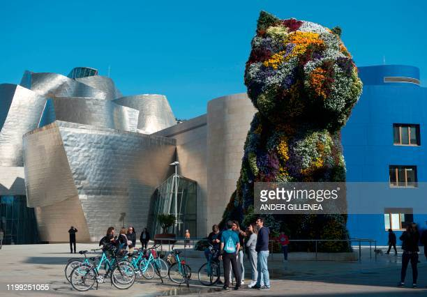 """Some people gather next to US artist Jeff Koons' sculpture """"Puppy"""" outside the Guggenheim Bilbao Museum in the Spanish Basque city of Bilbao, on..."""