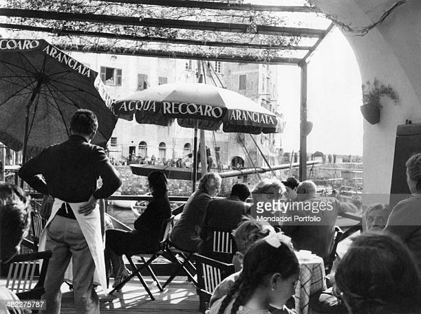 Some people gathered at the café waiting for the arrival of an enormous frying pan at the Fish Sagra Camogli 9th March 1954
