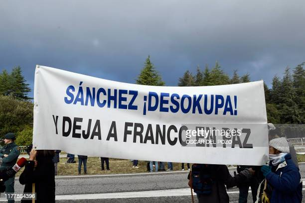 Some people hold a banner reading Sanchez go and leave Franco in peace during the exhumation of Spanish dictator Francisco Franco at the Valle de los...
