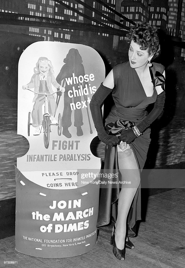 Some people keep their money in the silliest places. Gypsy Rose Lee pulls her gown up to fetch some dough for her contribution to the March of Dimes during fashion show at the Waldorf-Astoria.