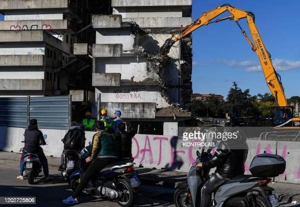 Some people look the demolition of the Green Sail building Vela Verde begins in Scampia in the suburb of Naples with two crawler excavators The...