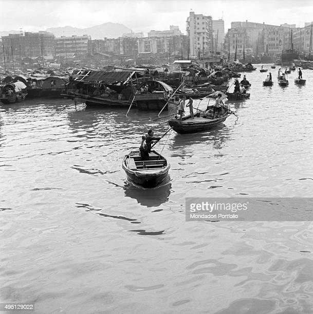 Some people moving by their rowing boats in the Aberdeen Harbour In the background many junks are moored Junks are the boats used by Chinese families...