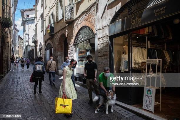 Some people pet a dog in the streets as they go about their day in the Upper Town on June 18, 2020 in Bergamo, Italy. The city of Bergamo is slowly...