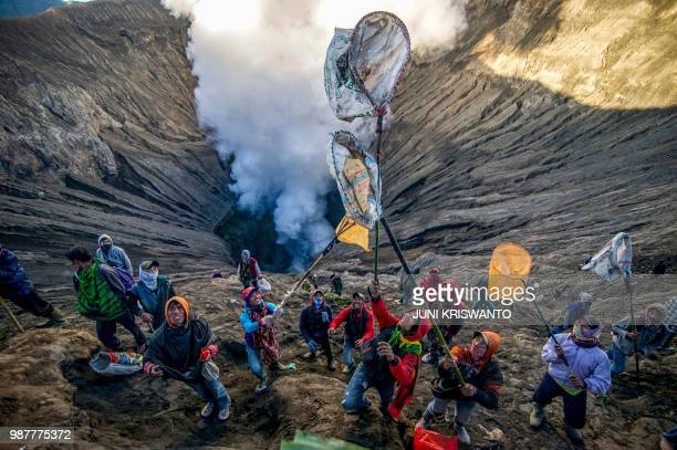 TOPSHOT Some people prepare to catch offerings thrown by Tengger tribe people into the crater of Bromo volcano to in Probolinggo East Java province...