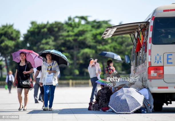 Some people sit on the ground in the shade of a van on July 12 2017 in Beijing China The dog days of summer start from July 12 in China