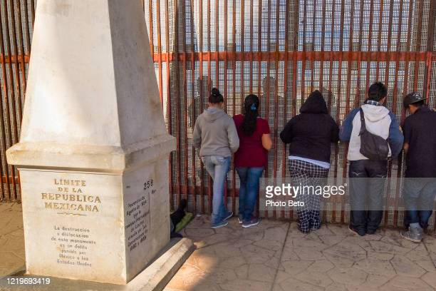 some people on the wall border between united states and mexico in tijuana - international match stock pictures, royalty-free photos & images