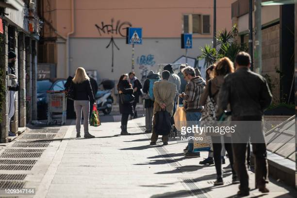Some people wait in line for their turn to enter a supermarket on April 7 2020 in Rome The Italian government has issued the nationwide lockdown...