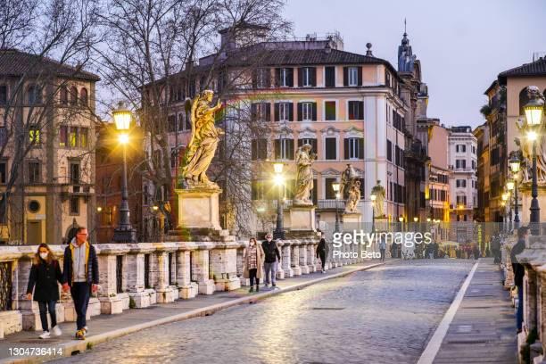 algunas personas caminan por ponte sant'angelo en roma en la época de covid-19 - distrito histórico fotografías e imágenes de stock