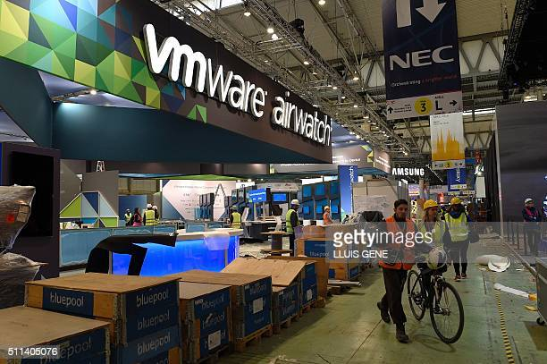 Some people walk past the VMware company stand as facilities for the Mobile World Congress in Barcelona are set up on February 20 before the start of...