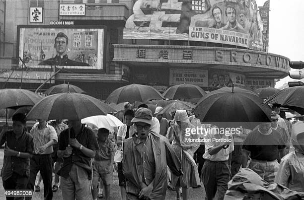 Some people walking protecting themselves from the rain by using raincoats and umbrellas In the background the cinema Broadway staging the film The...