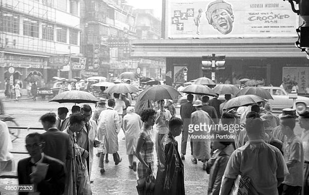 Some people walking protecting themselves from the rain by using raincoats and umbrellas In the background the poster of the film There Was a Crooked...