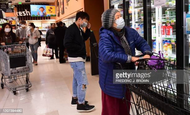 Some people wear facemasks while shopping for food at a Ralph's Supermarket in Monterey Park California on March 16 2020 as the Coronavirus pandemic...