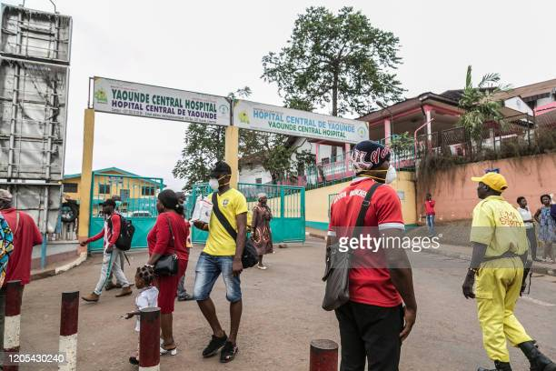 Some people wear masks as they walk by the entrance to the Yaounde General Hospital in Yaounde on March 6 2020 as Cameroon has confirmed its first...