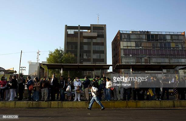 Some people wear protective masks as they stand at a bus stop May 6 2009 in Mexico City Mexico The government on Wednesday allowed restaurants and...