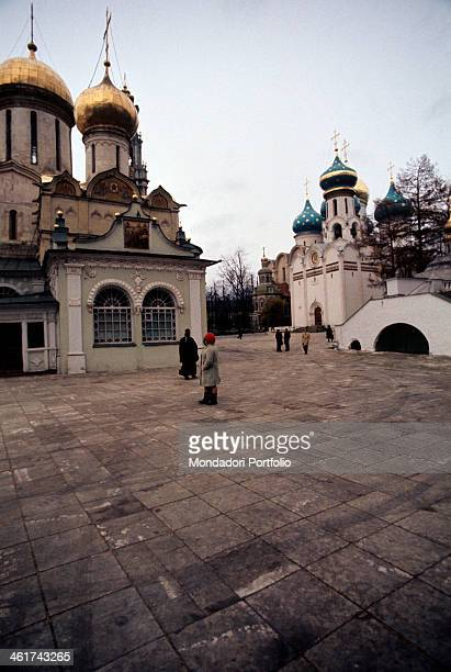 Some pilgrims and an orthodox monk walking in the little square of the Trinity Lavra overlooked by many religious buildings in the left foreground...