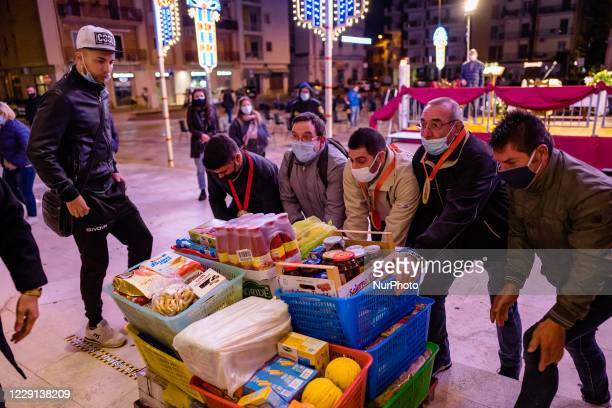 Some pilgrims from Bisceglie who came on foot from their city to honor the Santi Medici bring as a gift some basic necessities in the Basilica...