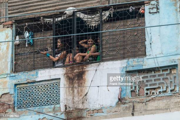 Some prostitutes looking out of a window secured with bars and waving to potential customers in New Delhi's Redlight District GBRoad in Ajmeri Gate...