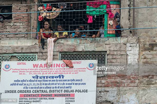 Some prostitutes looking out of a window secured with bars in New Delhi's Redlight District GBRoad in Ajmeri Gate area