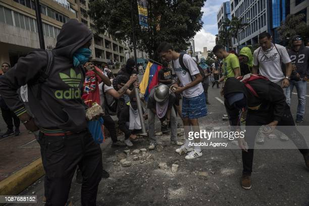 Some protesters collect stones to throw against Bolivarian police forces after Juan Guaido President of National Assembly declares himself interim...
