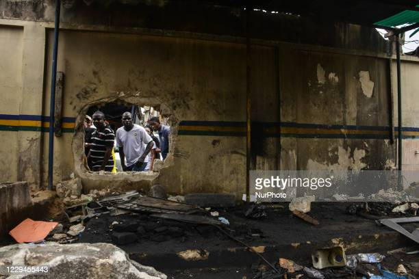 Some residents look through a destroyed property during the Inspector General Police visit to Lagos on November 3, 2020. The Inspector General of...
