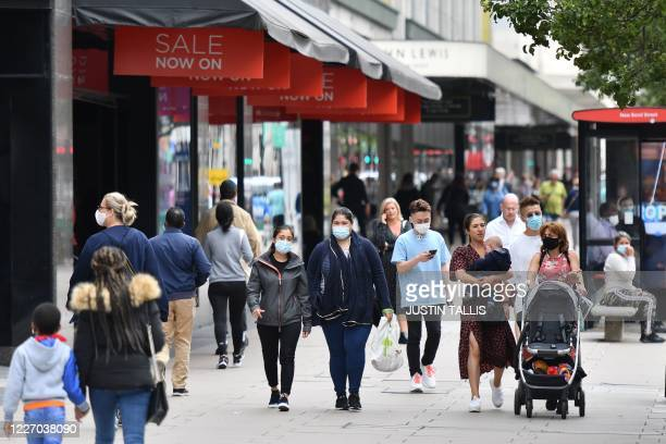 Some shoppers wear masks as a precaution against the transmission of the novel coronavirus as they walk along the pavement on Oxford Street in London...