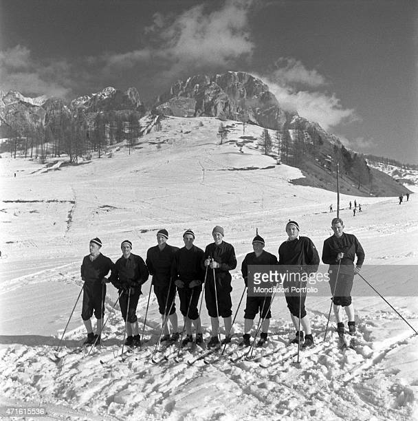 Some skiers posing in a line for a group photograph during the VII Olympic Winter Games Cortina d'Ampezzo 1956